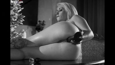 Пышная блондинка анально мастурбирует игрушкой на столе